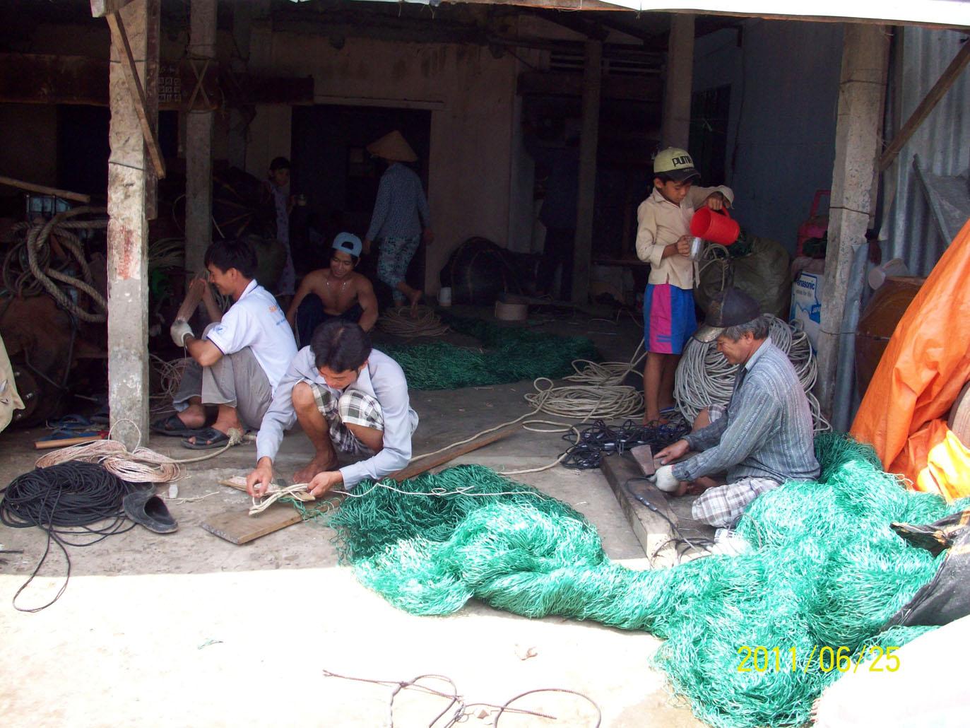 Ngư dân Gò Công vá lưới chuẩn bị ra khơi đánh bắt hải sản.