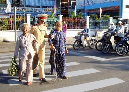 Chiến sĩ cảnh sát giao thông giúp người già qua đường.
