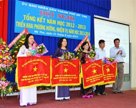 Ông  Nguyễn  Trọng Hữu,  Trưởng Ban Tuyên giáo  Thành ủy  Mỹ Tho  trao cờ  và tặng hoa  cho 4 đơn vị  đạt thành tích  xuất sắc  trong năm học 2012-2013.