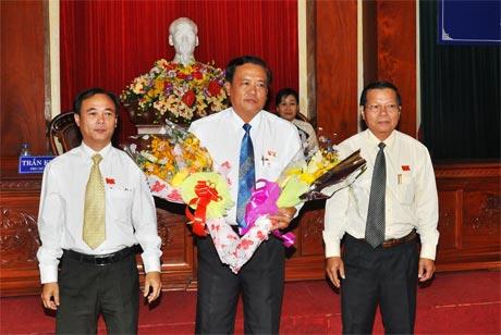 Chủ tịch UBND tỉnh Nguyễn Văn Khang và Phó Chủ tịch HĐND tỉnh Trần Kim Trát  tặng hoa chúc mừng tân Phó Chủ tịch UBND tỉnh Lê Văn Nghĩa.