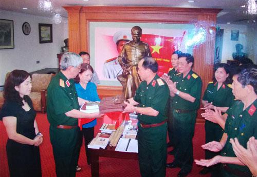 Trung tướng Mai Quang Phấn, Phó chủ nhiệm Tổng cục Chính trị trao tặng một số hiện vật cho gia đình Đại tướng Nguyễn Chí Thanh (10-2013).