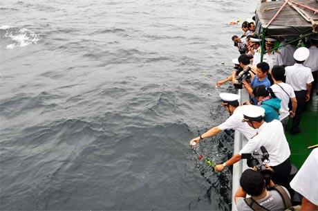 Các thành viên thực hiện nghi thức thả hoa xuống biển.