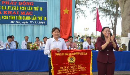 Bà Trần Kim Mai, Phó Chủ tịch UBND tỉnh trao Cờ Thi đua cùa Tổng LĐLĐ Việt Nam cho tập thể Công ty cổ phần may Sông Tiền.