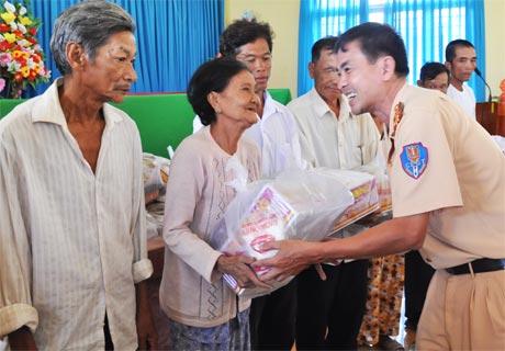 Thượng tá  Lê Hoàng Tiến, Phó Trưởng phòng PC 67 trao quà  cho hộ nghèo ở xã Phú Tân.
