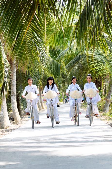 Học sinh đến trường trên tuyến đường liên ấp  thuộc xã Tân Phú, huyện Tân Phú Đông.