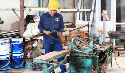 Anh Thuận bên máy uốn, nắn, bẻ đai sắt do anh sáng chế.