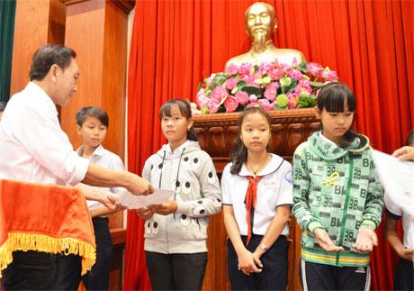 Ông Dương Ngọc Minh, Tổng Giám đốc công ty cổ phần Hùng Vương trao học bổng cho các học sinh có hoàn cảnh khó khăn.