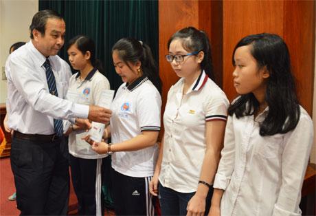 Ông Nguyễn Hữu Đức, nguyên Tổng Biên tập Báo Ấp Bắc trao học bổng cho học sinh các hoàn khó khăn.