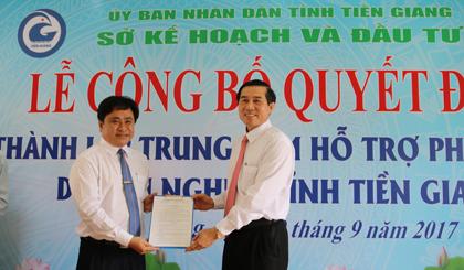 Ông Lê Văn Hưởng, Chủ tịch UBND tỉnh (bên phải) trao Quyết định của UBND tỉnh Tiền Giang về thành lập Trung tâm Hỗ trợ phát triển doanh nghiệp tỉnh Tiền Giang cho ông Trần Văn Dũng, Giám đốc Sở Kế hoạch và Đầu tư