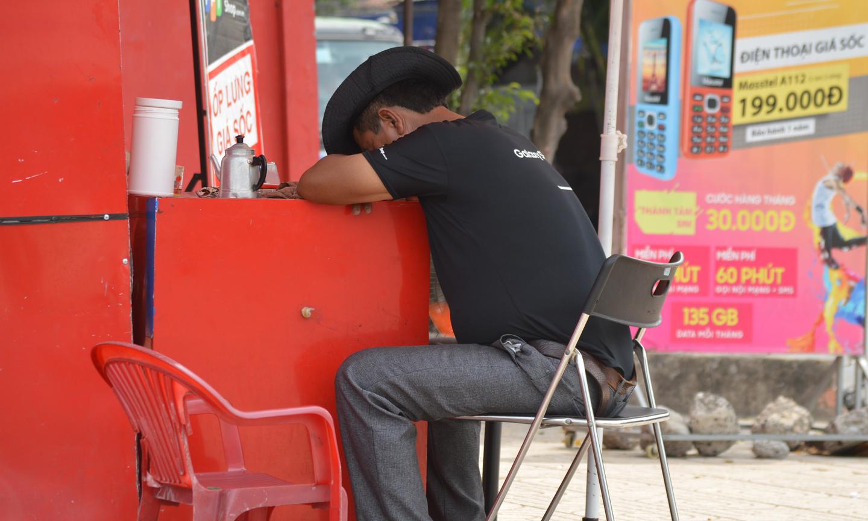 Bảo vệ cửa hàng tranh thủ núp nắng vào buổi trưa.