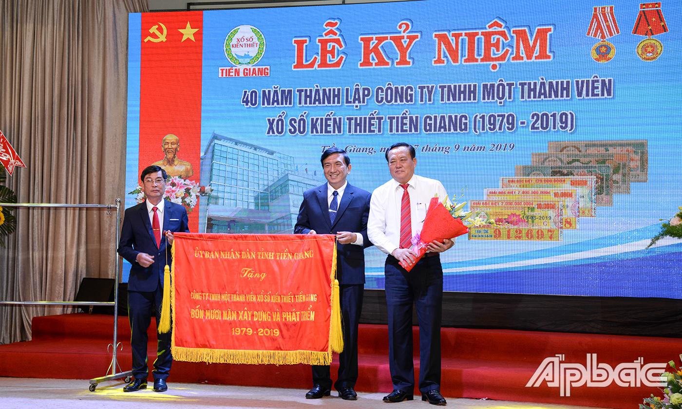 Đồng chí Lê Văn Nghĩa (bìa phải) trao bức trướng của UBND tỉnh cho Công ty TNHH Một thành viên XSKT Tiền Giang.