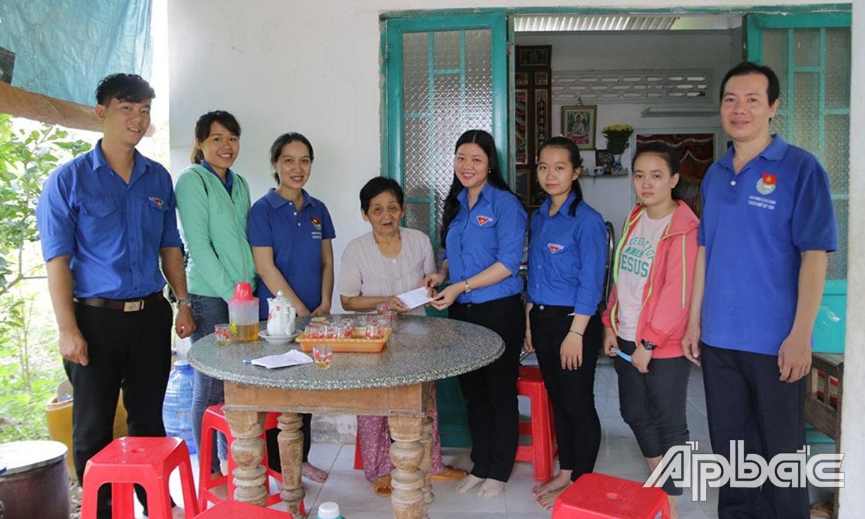 Chị Hương (thứ 4 từ phải qua) và ĐV-TN tặng quà cho gia đình  chính sách tại xã Thới Sơn (TP. Mỹ Tho).