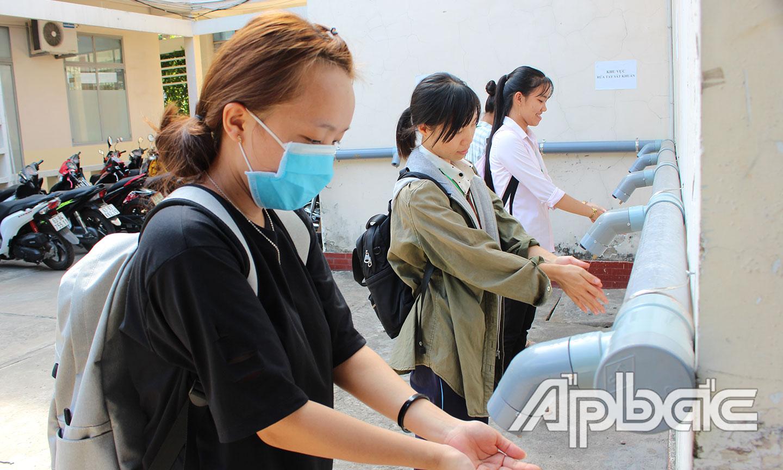 Sinh viên rửa tay sát khuẩn trước khi vào trường.