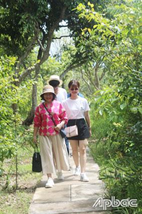 Du khách đi giữa vườn trái cây xanh mát của cù lao.